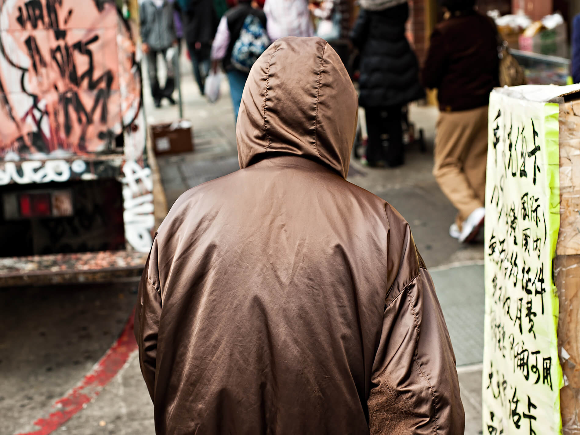 Hooded man walking through Chinatown, San Francisco