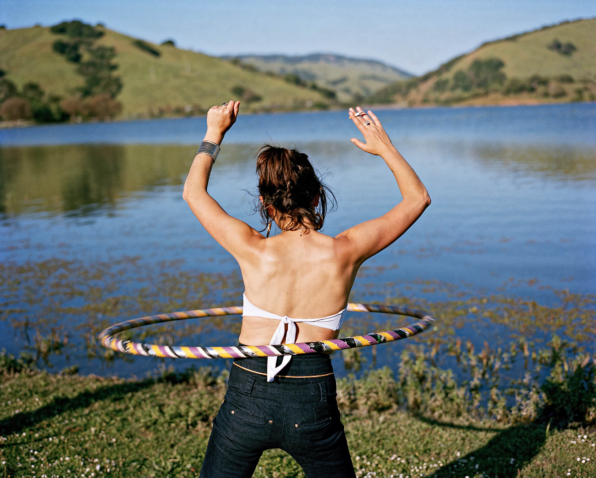Woman with hula hoop and cigarette at lake