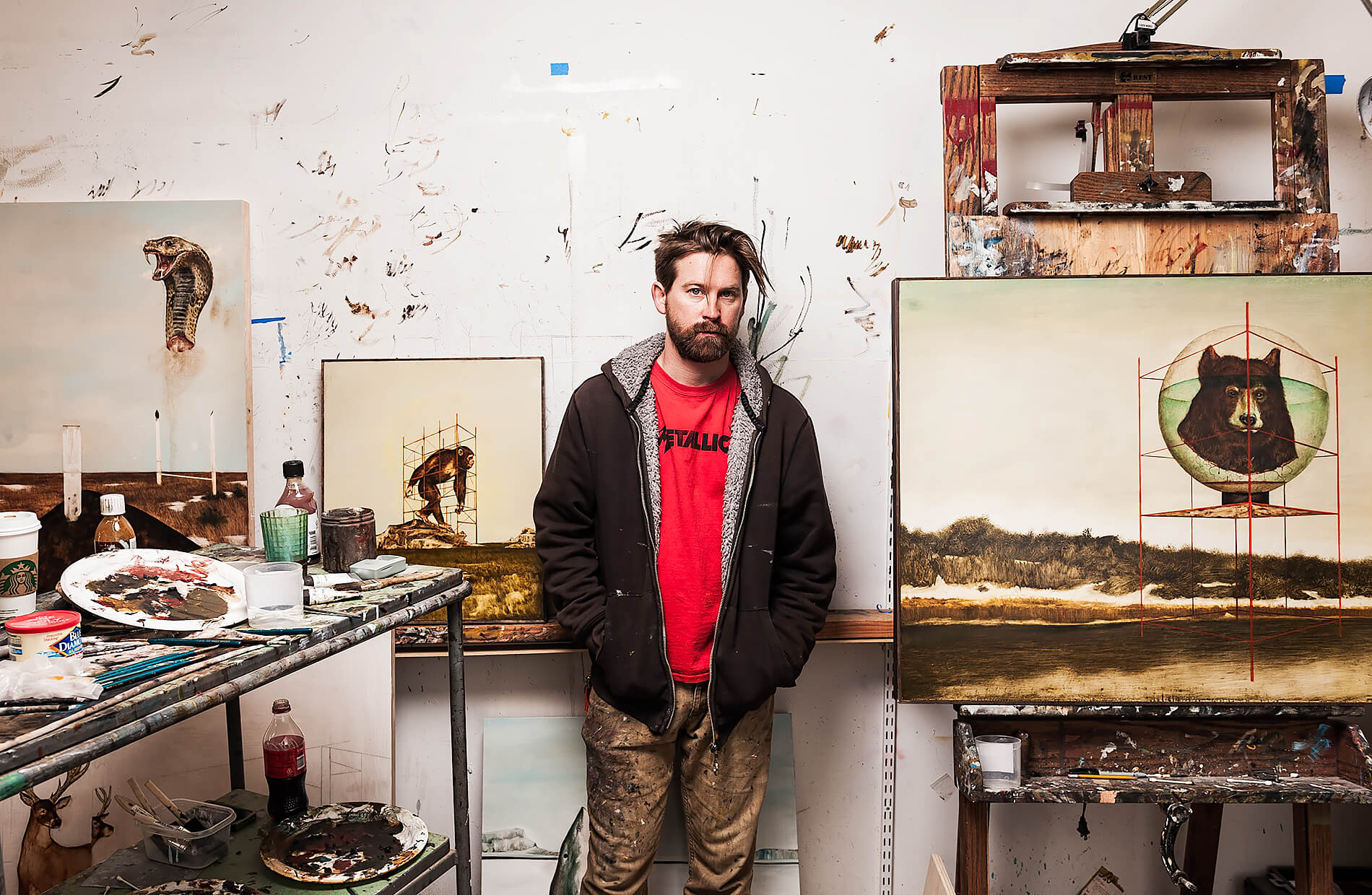 Artist Kevin Taylor surrounded by paintings in his San Francisco studio.