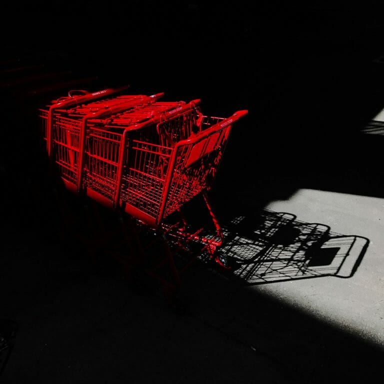 Red shopping carts with shadows on concrete.
