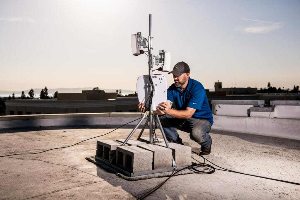 Jonathan Weinberg of Common Networks inspects an antenna installed on the roof of the Alameda Theatre & Cineplex, the tallest building in Alameda, CA.