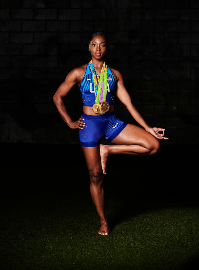 Tianna Bartoletta does yoga pose with her gold medals